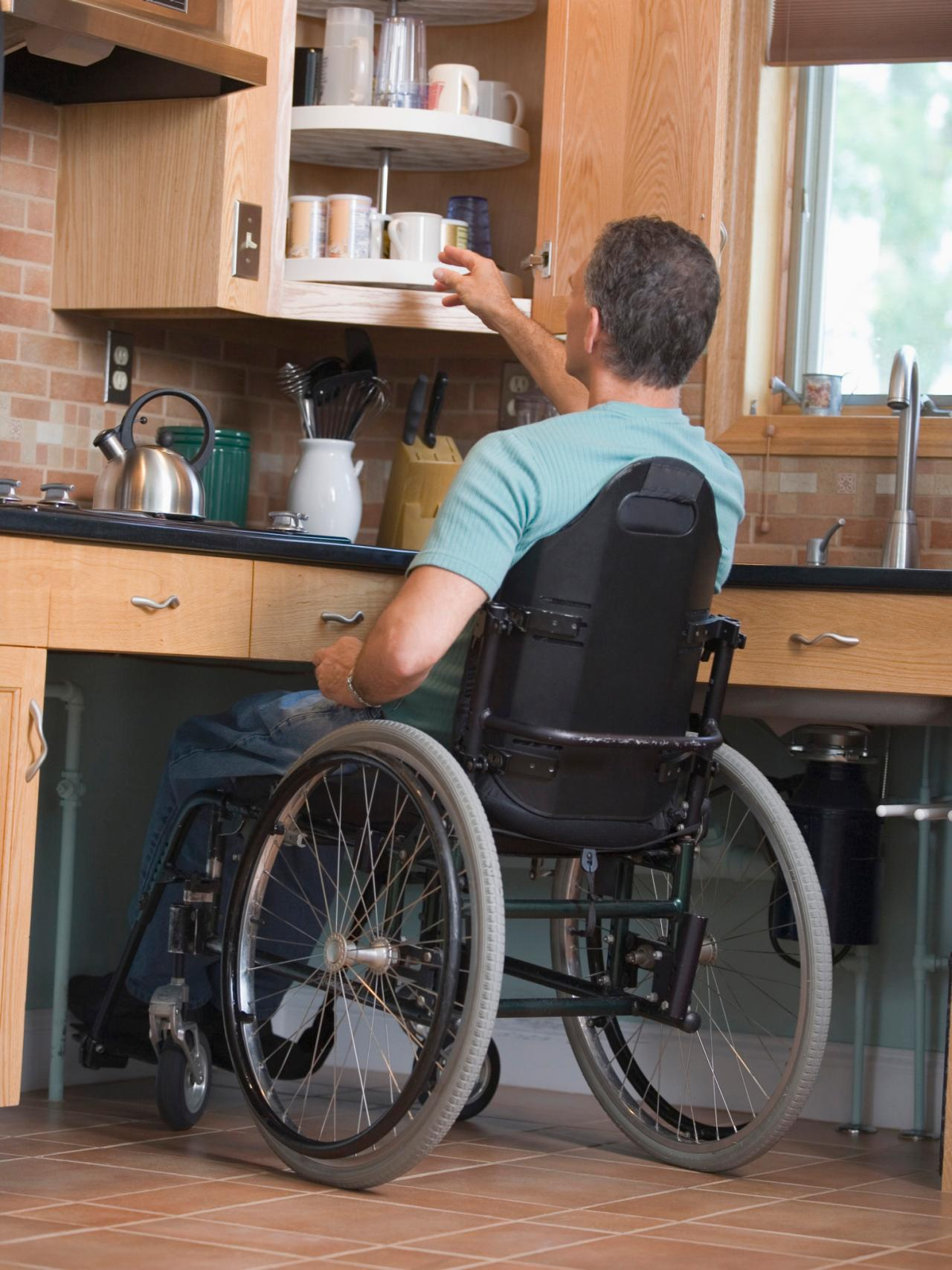 man reaching in a cupboard in his accessible kitchen