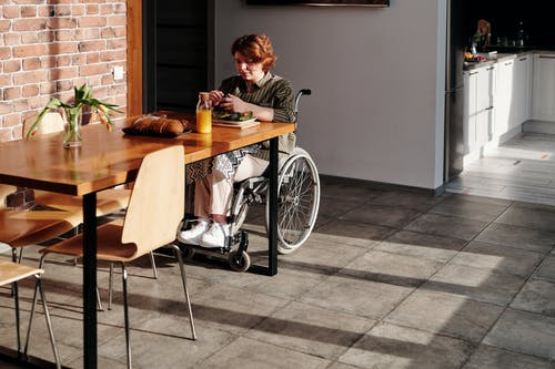 Stay safe: Coronavirus guide Woman in a wheelchair eating alone at table